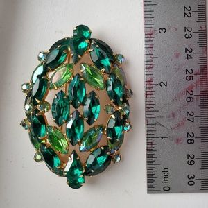 Vintage emerald colored stones brooch